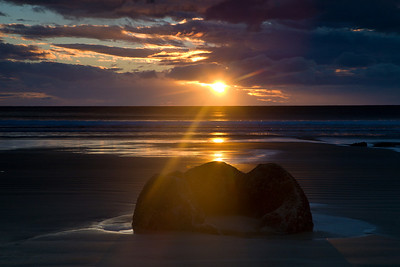 Sunrise at Moeraki, 40 kilometres south of Oamaru, huge spherical boulders are scattered along the beach. Others can be seen emerging from the sandstone cliffs. Each boulder weighs several tonnes and is up to two metres high.  New Zealand